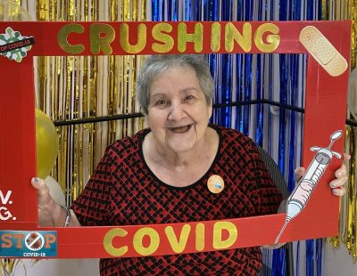 """Gail holding a """"crushing COVID"""" sign at Victoria Gardens long term care home"""
